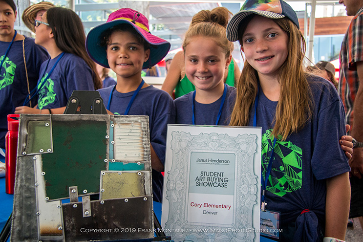Three students smiling with metal artwork they bought for their school through the CherryArts Student Art Buying Program