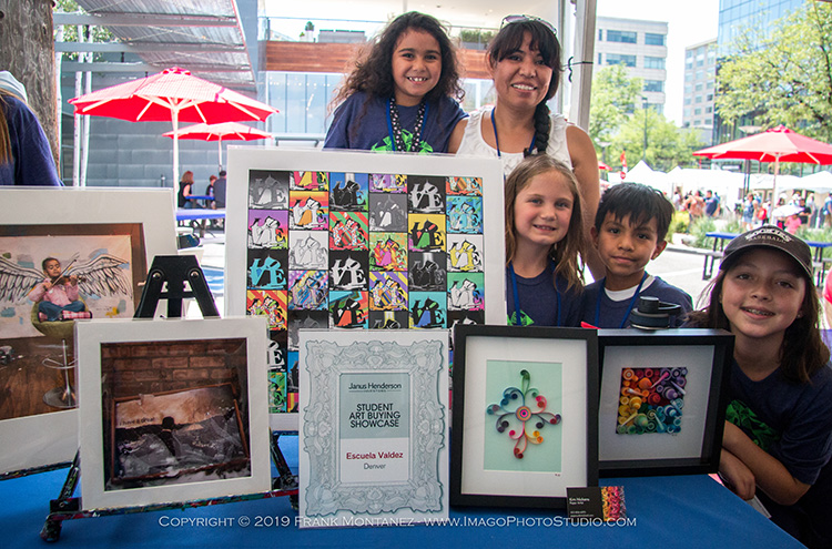 A teacher and students with the art purchased for their school, including photography and mixed media